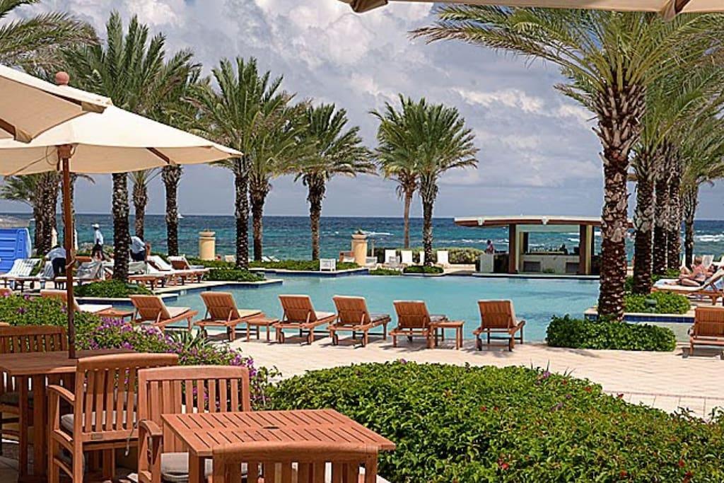 Piscine et jakousi avec transats et parasols vue sur le bar de la plage et océan