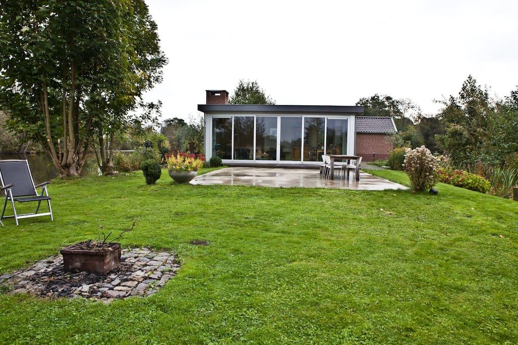 Buitenvuur-stookplaats met zicht op terras en voorgevel van het huis.