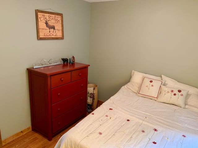 This bedroom has a dresser, and full size bed