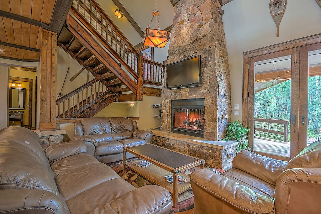 The living area features a beautiful stone gas fireplace and a mounted flat screen TV.