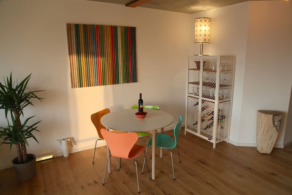 dining area with designer chairs and wine cabinet made from wire mesh.