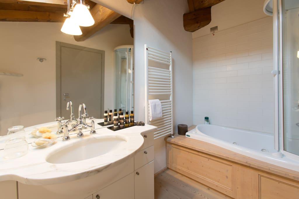 Bagno privato con vasca idromassaggio e cabina doccia.
