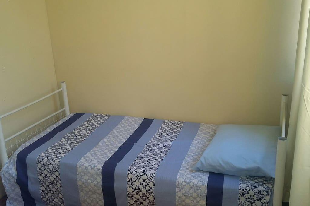 Quarto com cama de solteiro, armario e ventilador