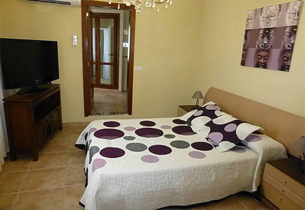 Habitación con cama doble y baño de la habitación al fondo