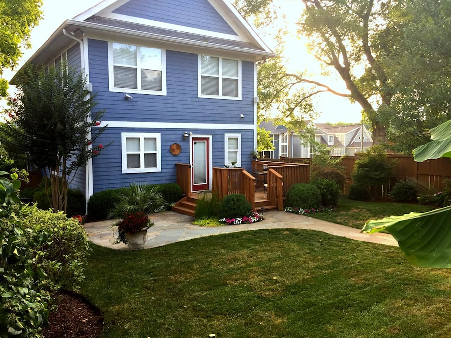 Private Fenced in backyard with deck and patio, grill, lush landscaping.
