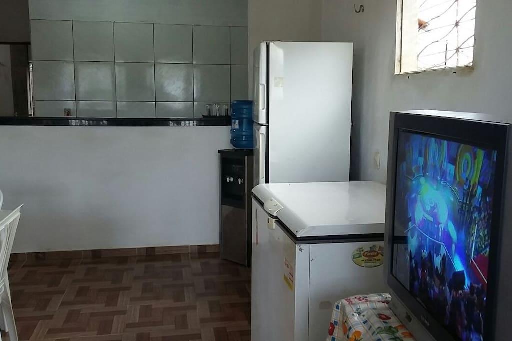 Sala ampla com geladeira, freezer, sofás, cadeiras e televisão.