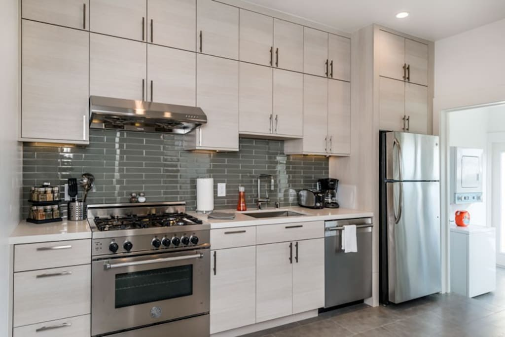 Remodeled kitchen with new European stainless steel appliances, quartz counter tops & glass tile backsplash.