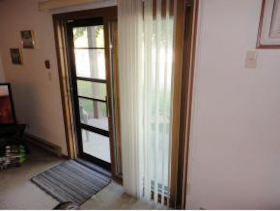 Patio doors let in natural light when looking out from the  ground floor condo!   There is also a front door to the condo which is to the right of this door.