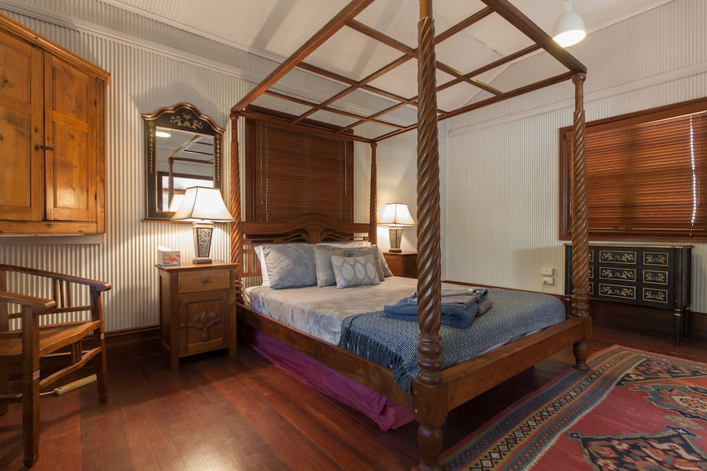 Warm and inviting; the main bedroom with four poster antique bed
