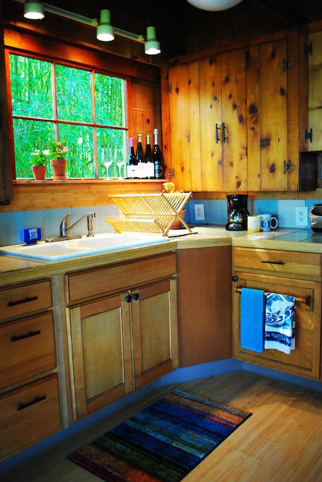 Kitchen includes teapot, coffee maker, refrigerator, oven/stovetop
