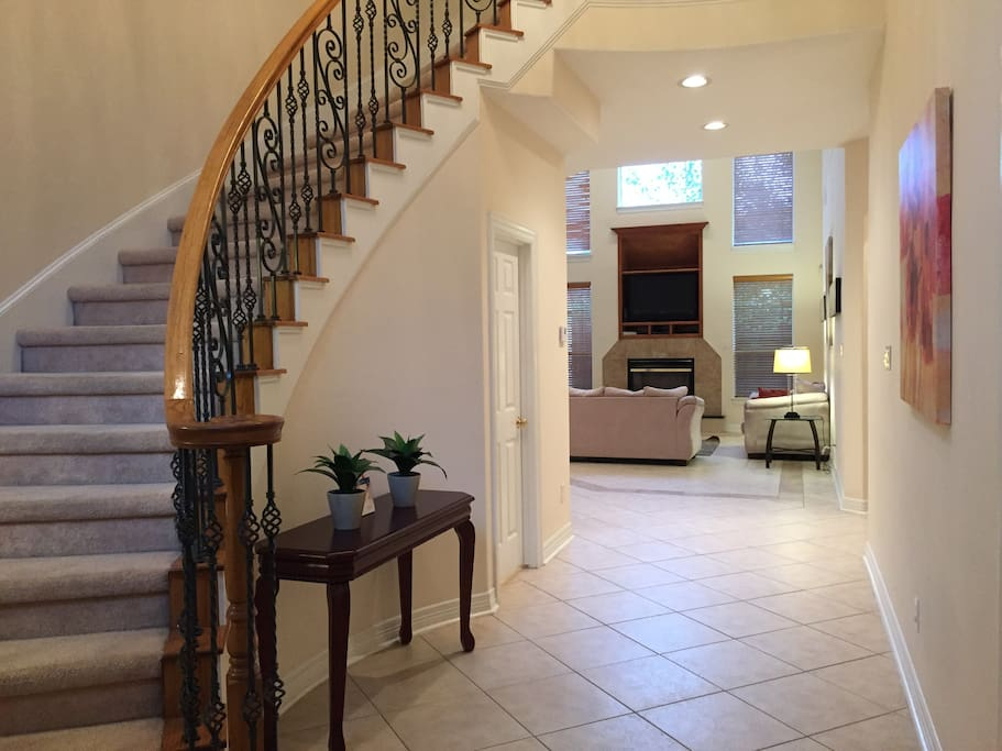 Entry with powder room under stairs.