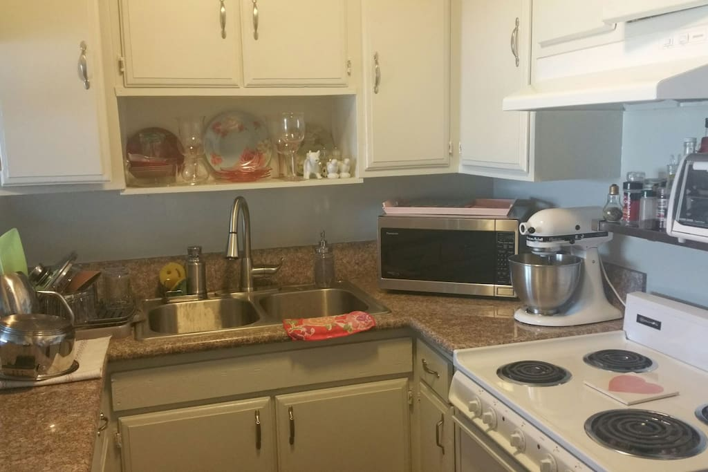 Fully loaded kitchen with electric stove, microwave, coffee maker, toaster oven and Ninja blender