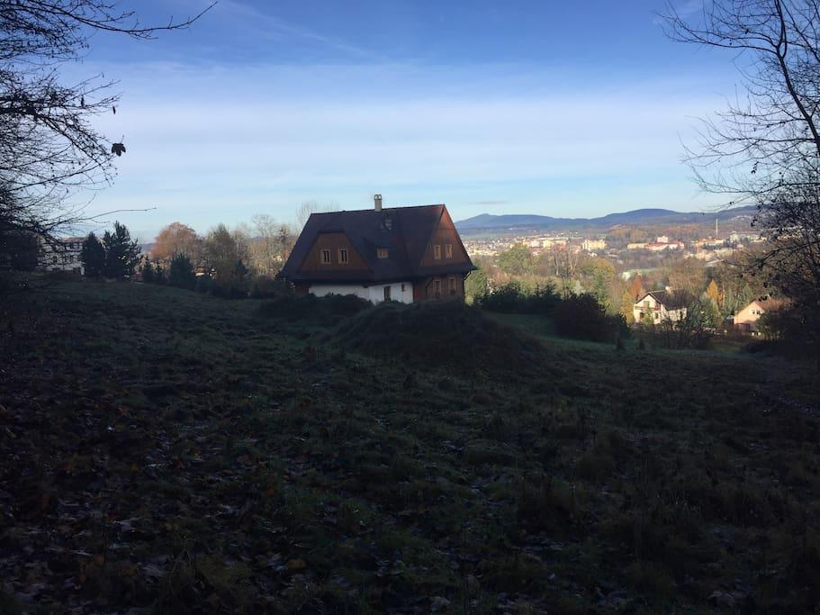 Pohled na chaloupku a okolí z lesa u hradu Valdštejn