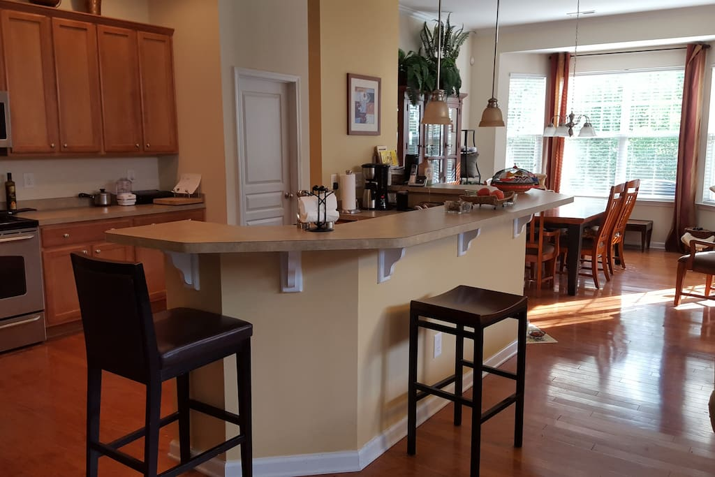Kitchen with large bar for meals or snacks.