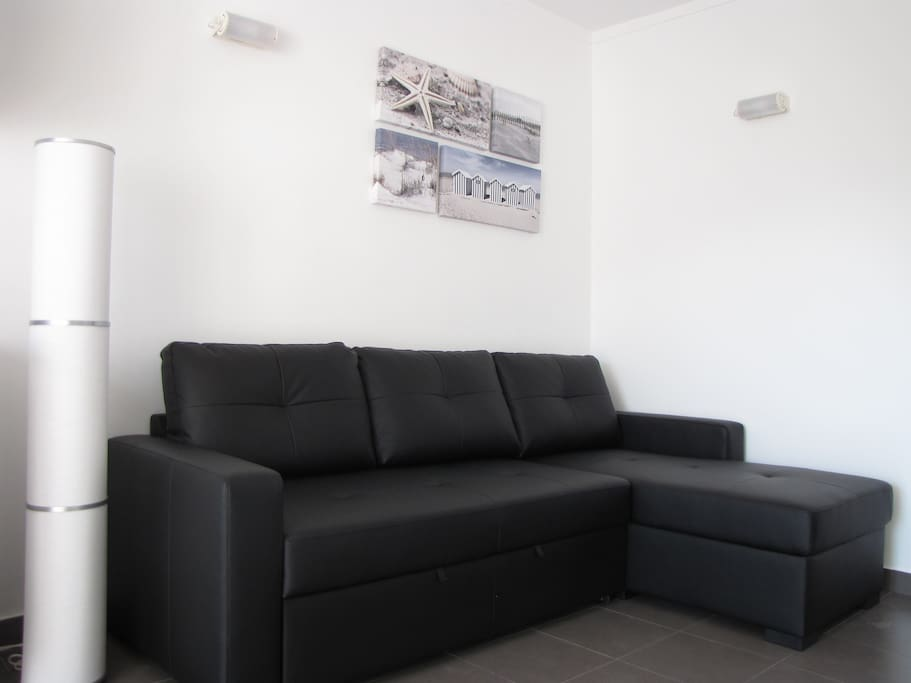 Sala com Sofá-cama em pele e TV Led com canais por cabo