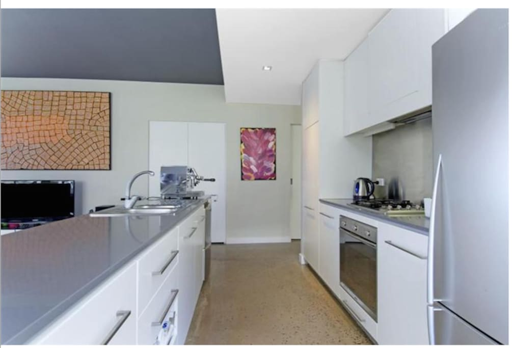 Spacious kitchen area with marble bench top, full oven and microwave.
