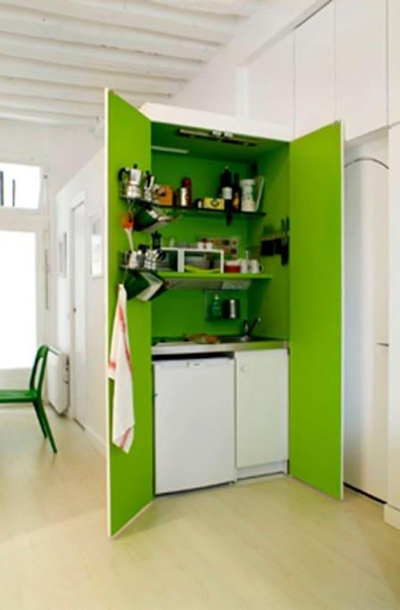 Cucina dentro armadio:1 microonde, 1 caffettiera elettrica,2 piastre elettriche,1 lavello, frigo con comparto ghiaccio, pentole, padelle, macchine da caffe italiane, piatti, bicchieri, posate per 6