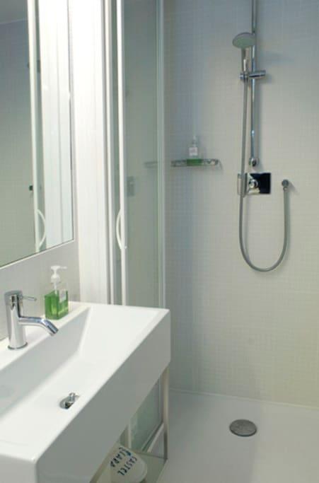 Bagno con grande doccia, wc con doccetta, lavandino sospeso con ripiano