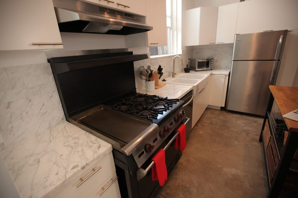 The kitchen with pots and pans, marble counters, wolf stove, full sized stainless fridge, where you can also bring home your delicious leftovers from all the local restaurants.