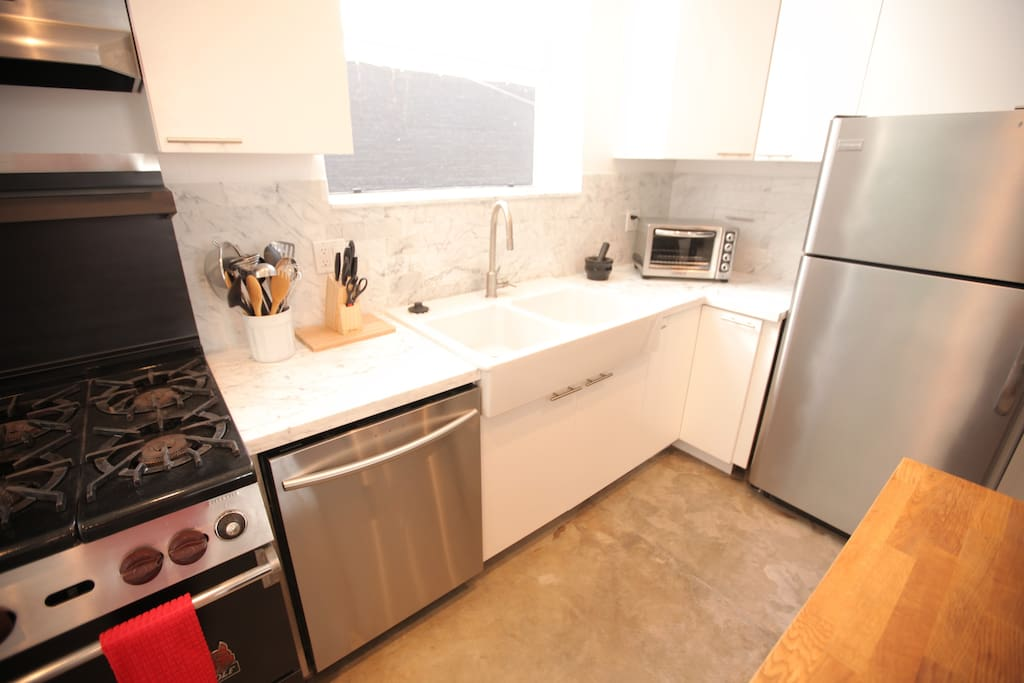 Large farm sink, KitchenAid Toaster oven, garbage disposal, full sized dishwasher, cabinets filled with plates, cups, glasses, mugs, cookie sheets, pots and pans, knives, kitchen tools, and utensils.  Under the sink are cleaning supplies.