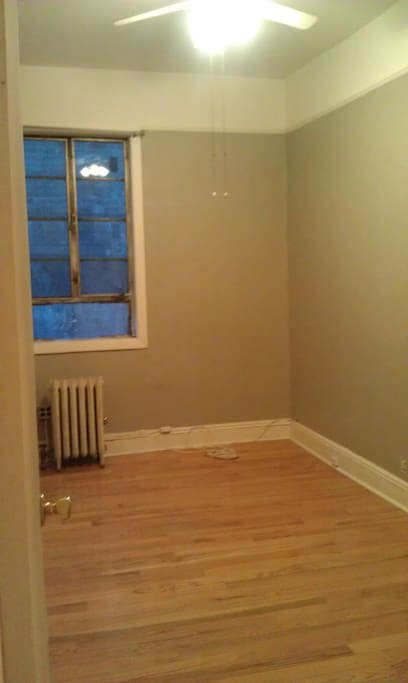 The room is currently furnished with a full-size futon, a small bookshelf, and an armchair.