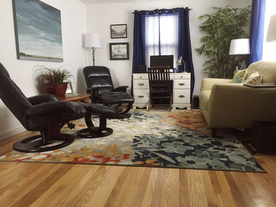 Fully furnished living room with comfortable seating and a computer
