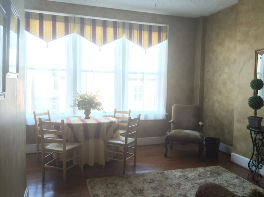 Breakfast room includes four person table, arm chair, and a couch with a pullout full size bed