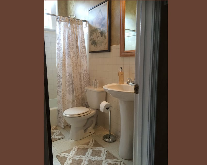 Bathroom includes tub/shower, tiled walls and toiletries.