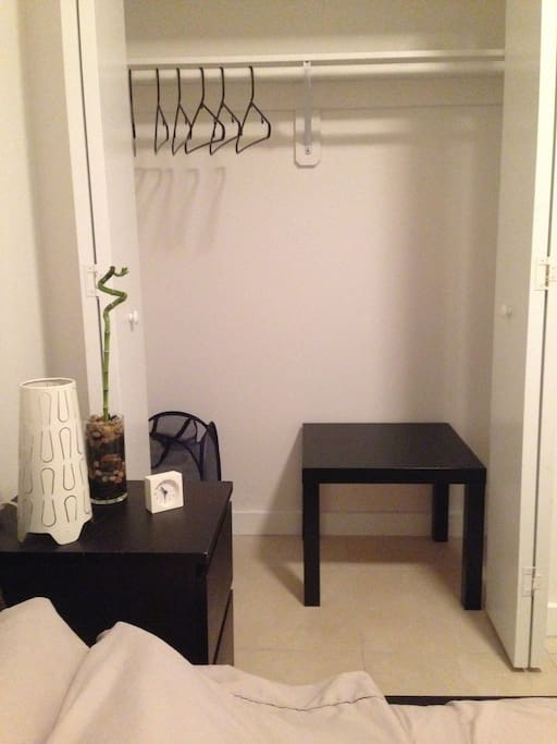 Closet with complementary hangers, luggage stand, and hamper