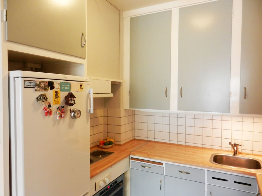Small, but functional kitchen with refrigerator, freezer, dish washer, washing machine, oven and two hot plates.