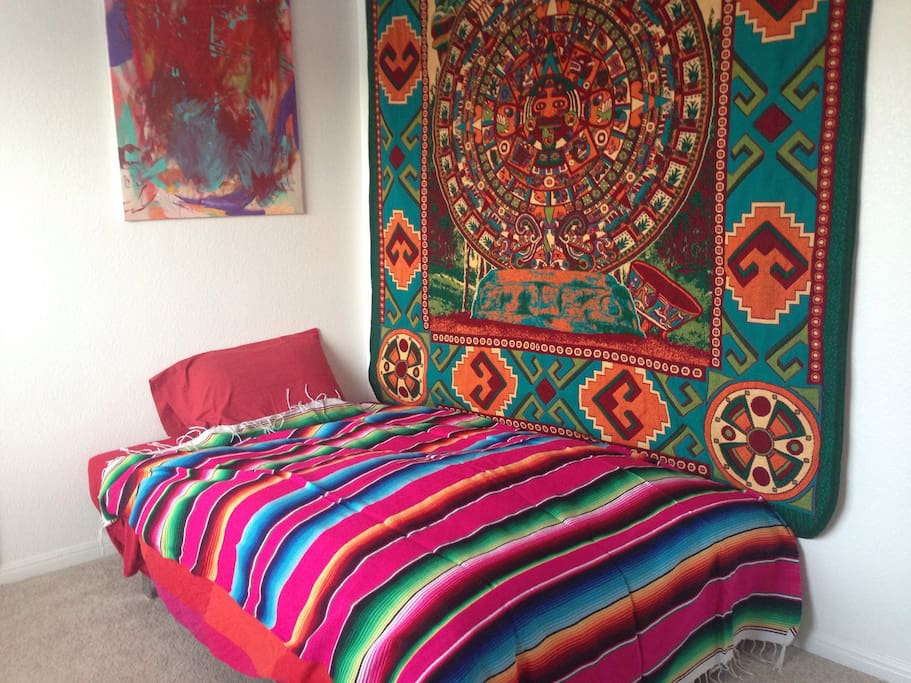 Traveler's room with woven blankets from Mexico, pillows from Thailand, comforter with swan feathers from Austria