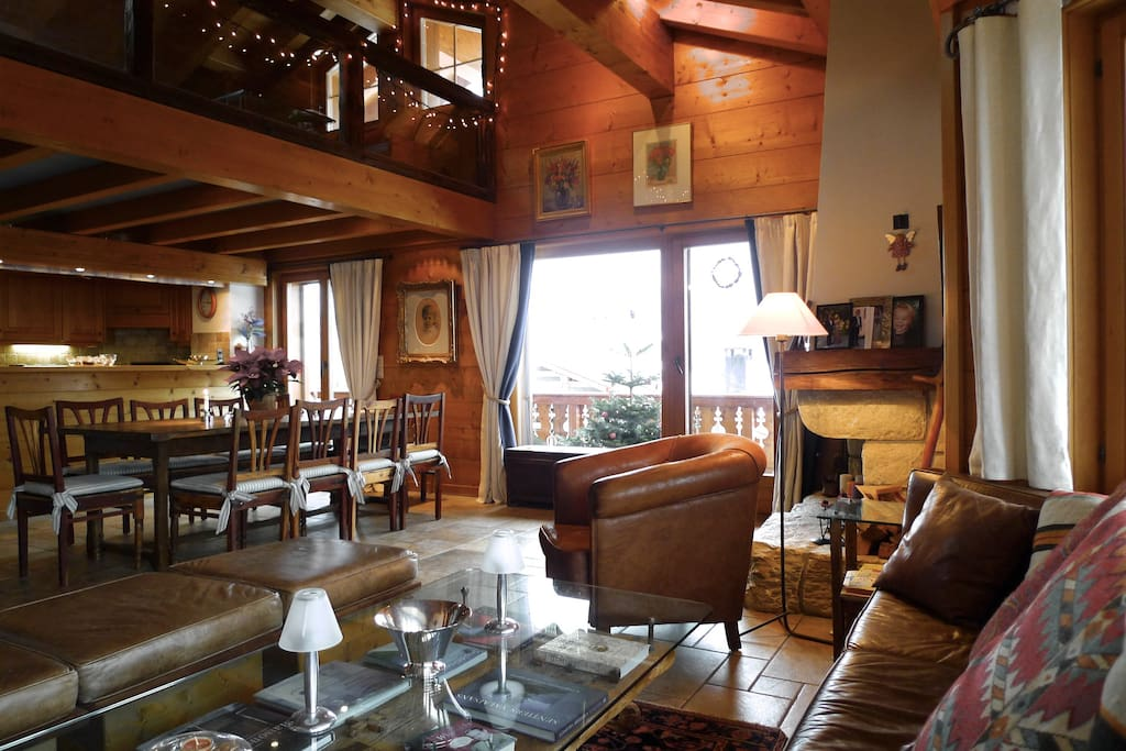 Living room with bar kitchen, plenty of seating and a fireplace. Mezzanine w TV corner above.