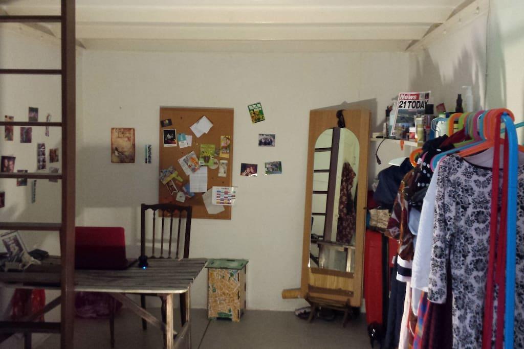Bottom floor of room: desk, shelves, clothes rail, general living area