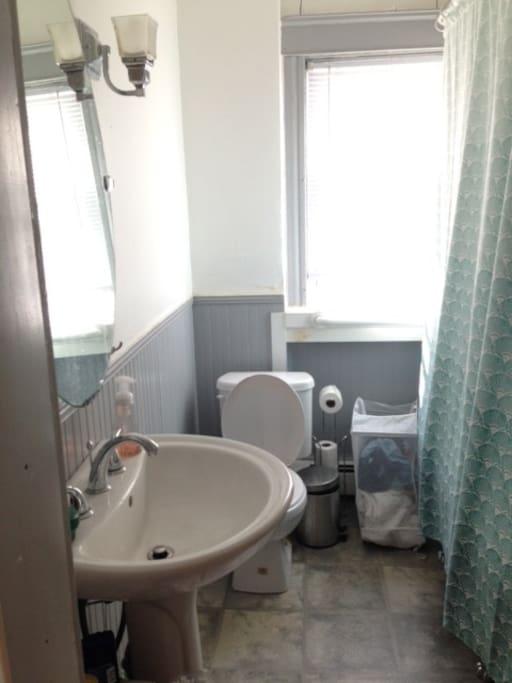 Clawfoot tub in a cute and bright bathroom