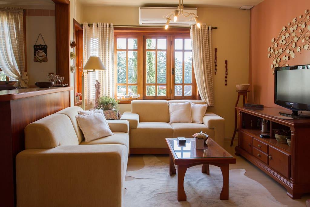 Sala de estar e TV, com bancada da cozinha.