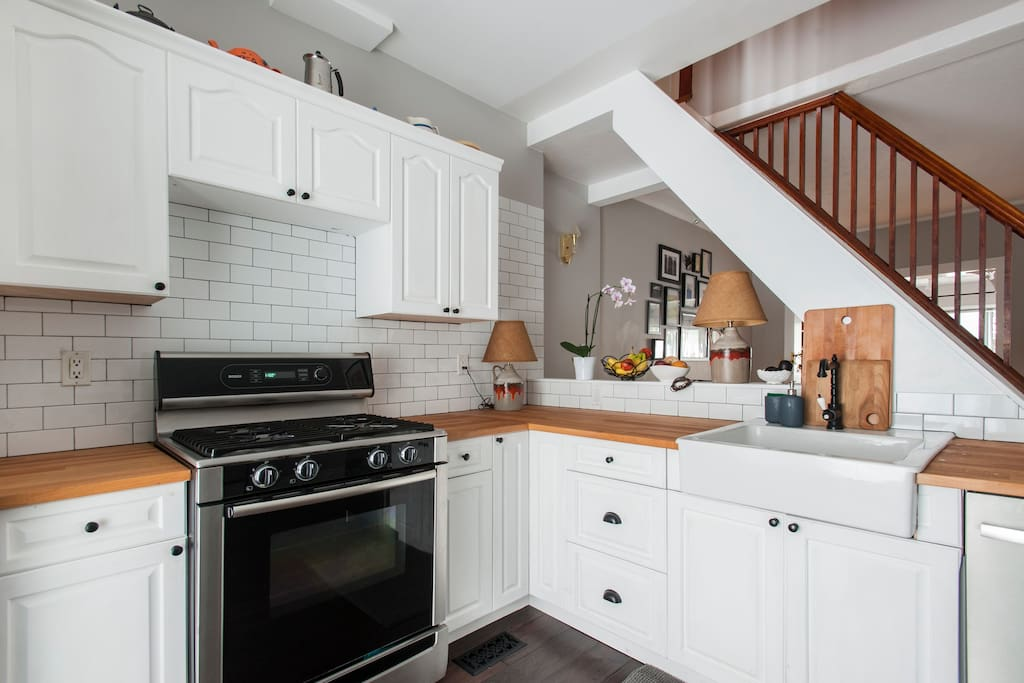 Open concept kitchen with stainless gas stove, microwave, dishwasher, and full size fridge