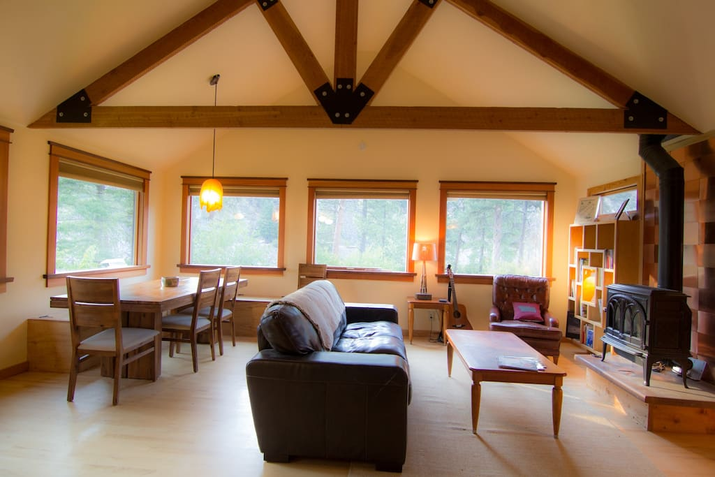 Relaxing living/dining area. Enjoy wrap-around views of the river next to the propane fireplace.