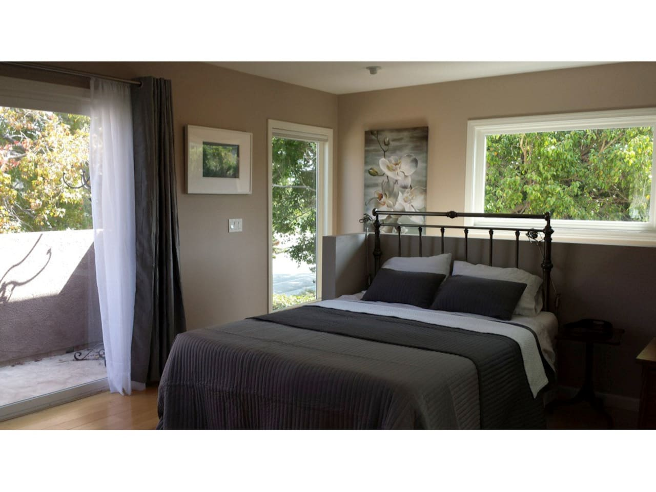 Luxury bedding on a queen size memory foam tempurpedic mattress with complete privacy out every window.