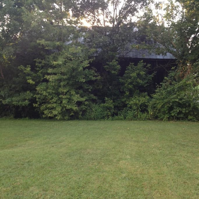 Beautiful level lot to pitch your tent or park your camper. A small creek runs between the lot and the historical barn in the background.