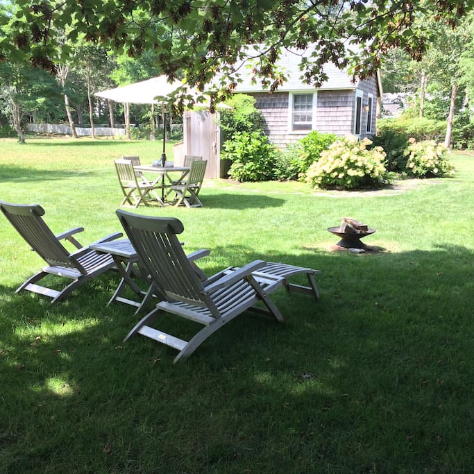 Private lawn area with lounge chairs, table & chairs, Weber grill, fire pit.