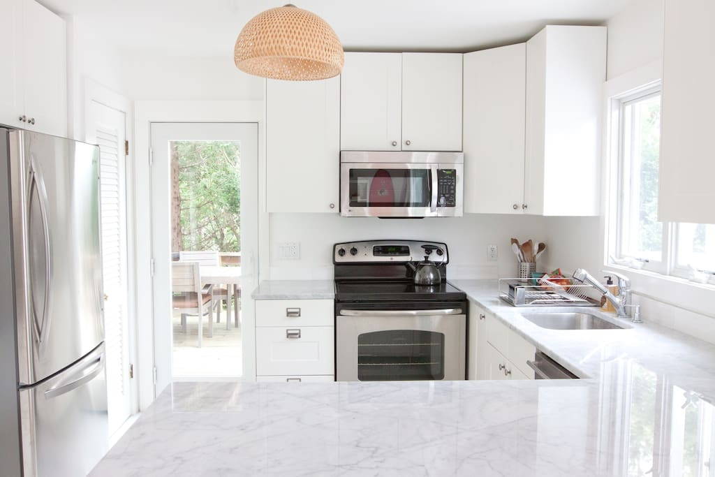 Kitchen with Breakfast Bar | White Carrera Polished Marble Counters + Floors | White laquer kitchen shelves | Door to side deck