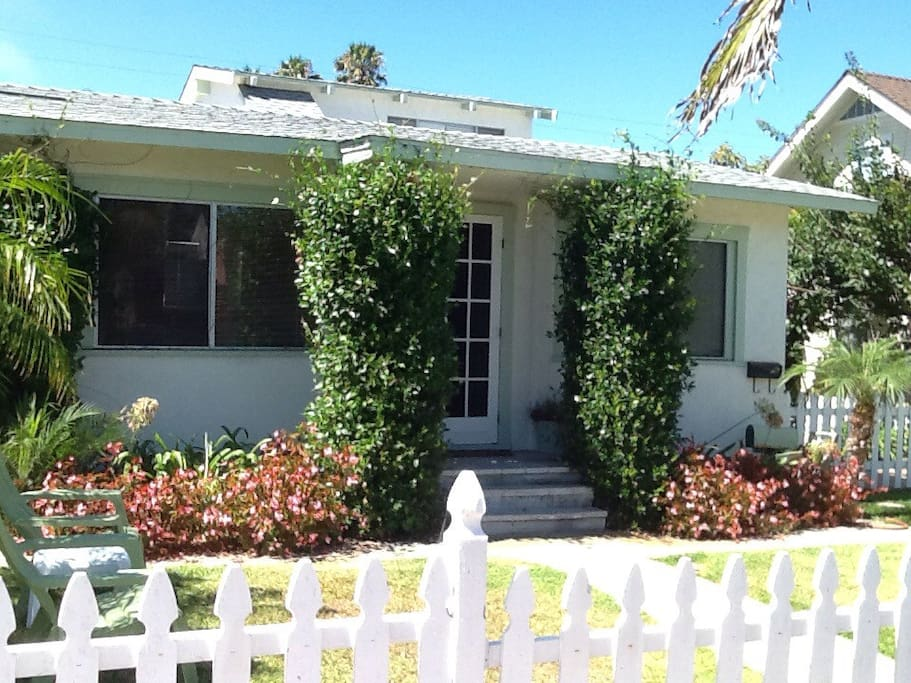 Nice front yard with green grass and a white picket fence.