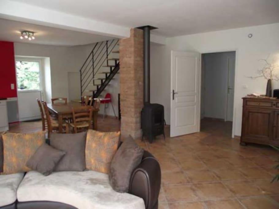 Grande pièce à vivre très conviviale avec poële à bois au centre de la pièce