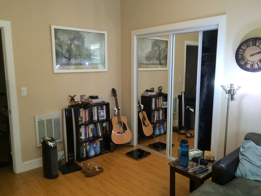 Spacious room with a plethora of books and a guitar to relax with :)