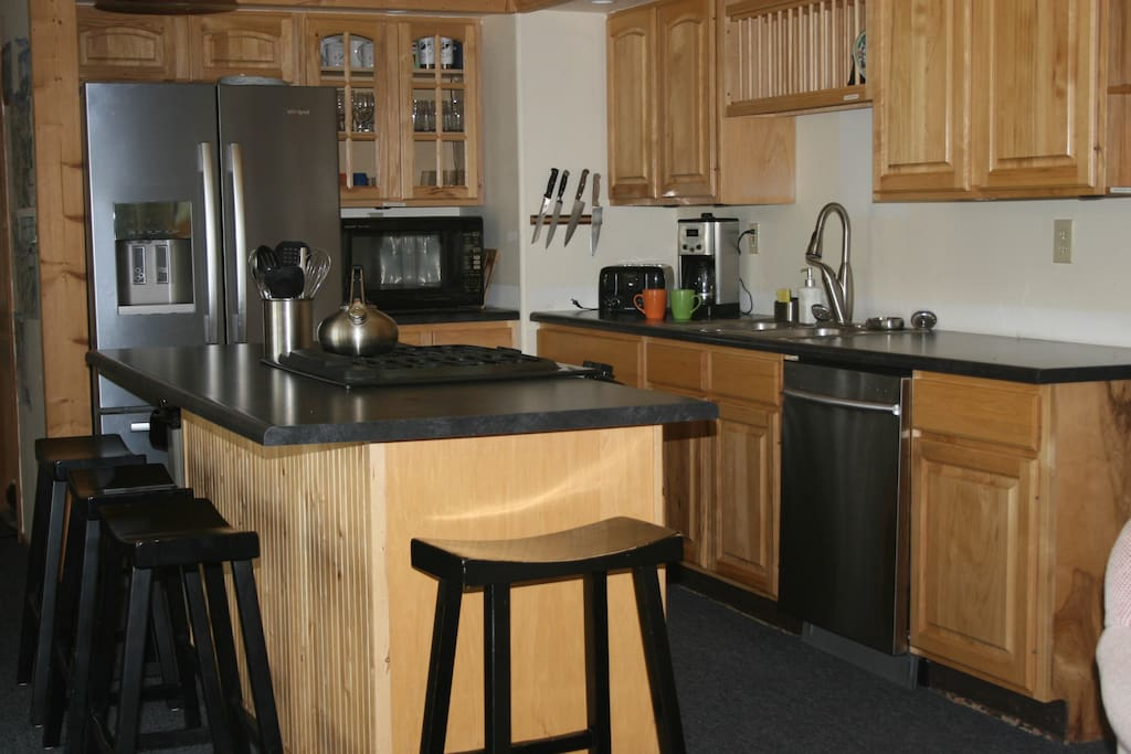 Gourmet stainless steel kitchen w/ gas stove in center island.