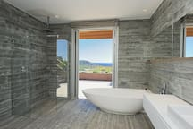 A large walk-in shower and a bath with a view ...