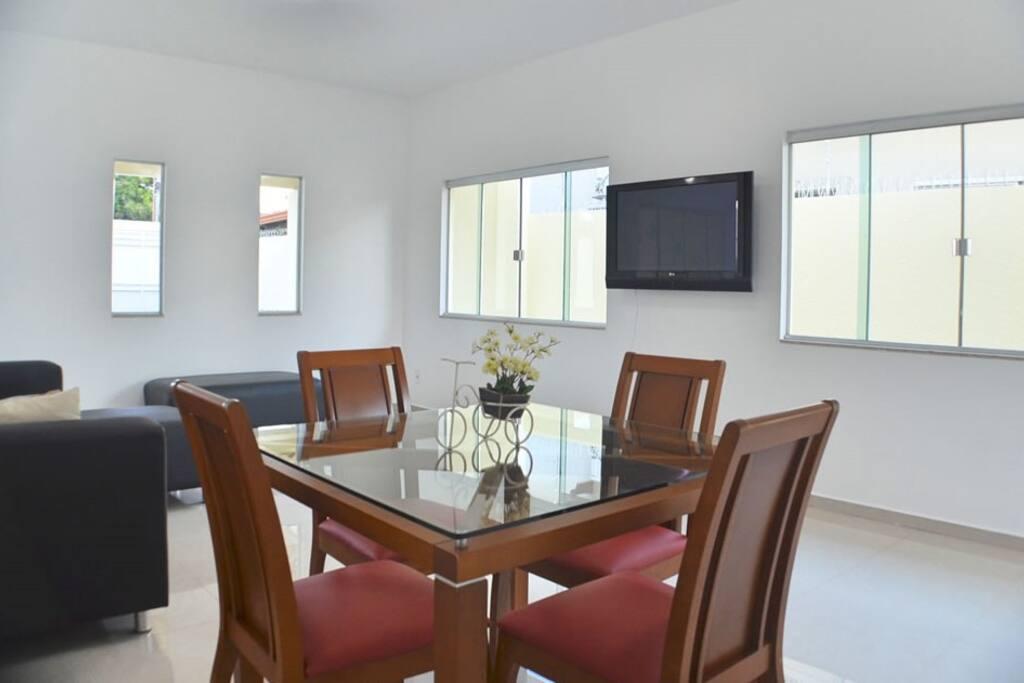 Ampla sala com TV, sofá e mesa de jantar.