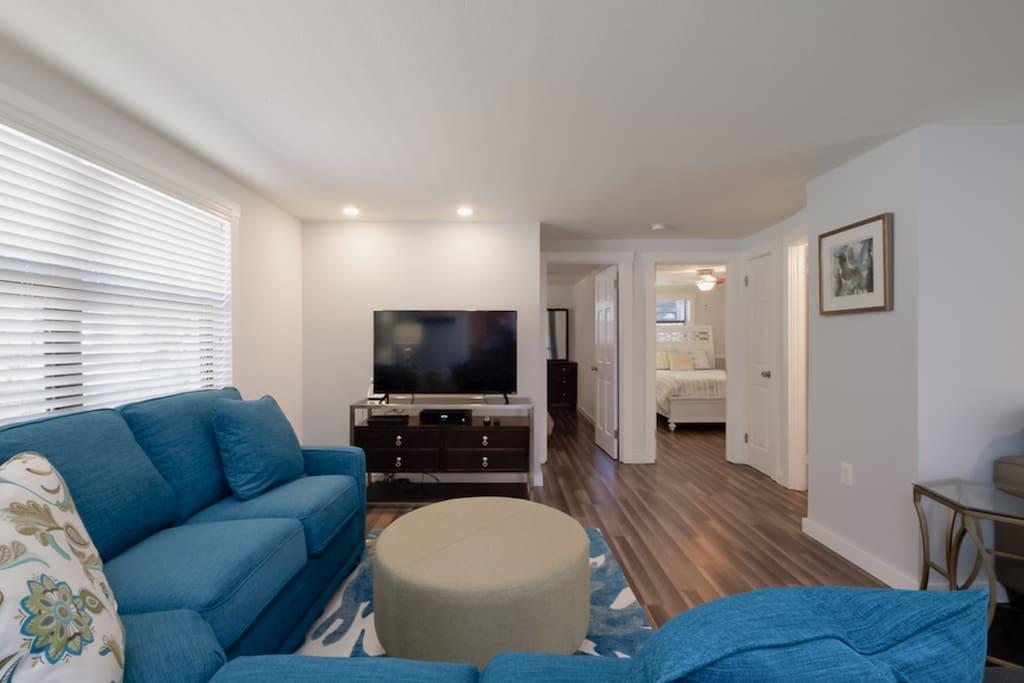 """The living room holds a comfy sectional and 50"""" flat screen TV for nights in."""