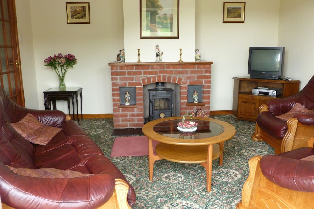 comfy lounge with log burner. Patio doors with lovely views down the valley.