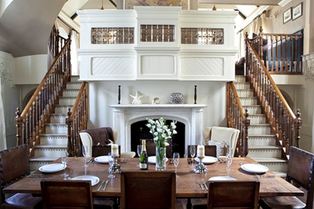Dining Hall with the original chapel pulpit, custom silk drapery, solid oak floors and marble fireplace. A exquisite dining table for eight, ideal for intimate crackling fire side supper parties.